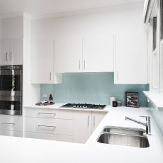 White cabinets with glass splash back